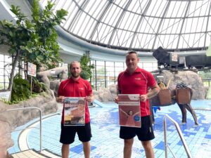 Weltkindertag im Aquapark Oberhausen: Männer mit Plakat vor Schwimmbecken