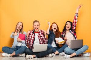 Studium, Ausbildung oder beides? Gruppe Jugendlicher vor gelber wand